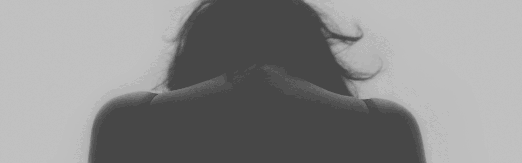 black and white photo of the back of a woman with her head down.