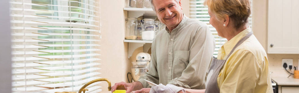 Caring for loved one – couple washing dishes together