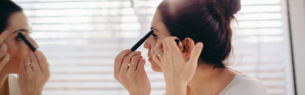 woman looking in mirror putting on makeup