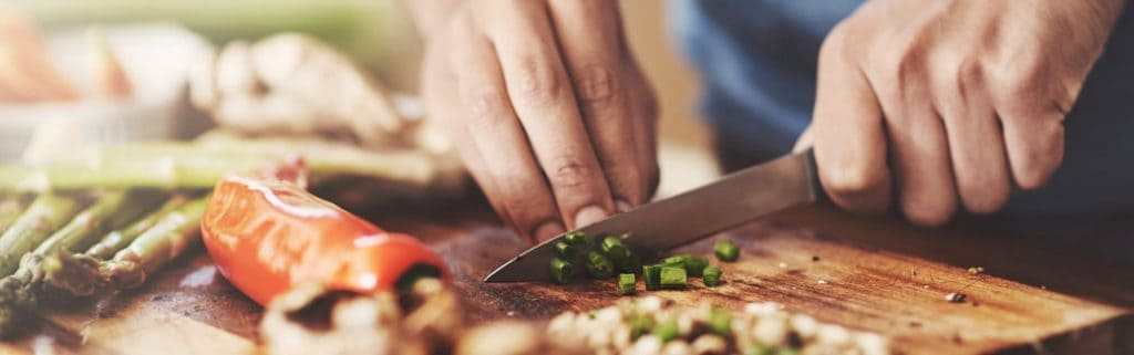 close-up of man chopping green onions